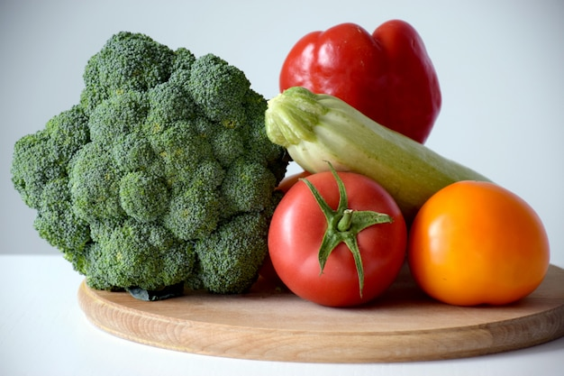Assortment of healthy food ingredients for cooking on a wooden cutting board. organic vegetables: broccoli, tomato, zucchini and pepper. balanced nutrition or dieting concept.