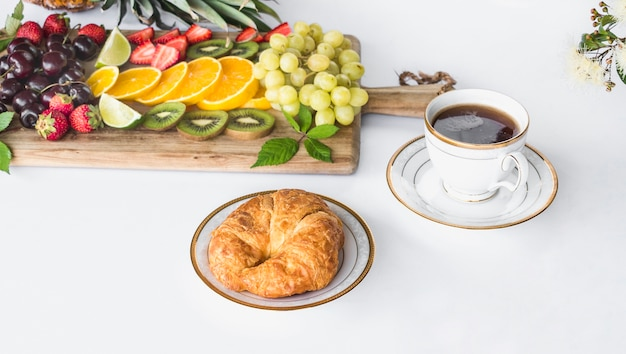 Assortment of healthy fruits with bread and tea cup on white background