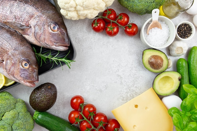 Assortment of healthy ketogenic low carb food ingredients for cooking. vegetables, meat, fish, cheese and eggs.