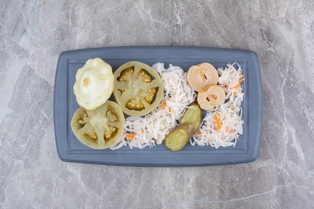 Assortment of homemade pickles on dark plate.