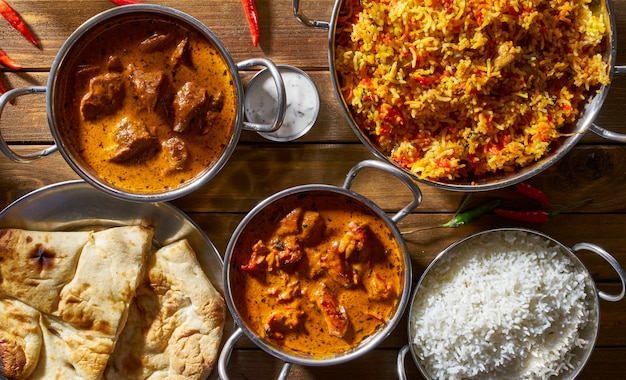 An assortment of indian dishes including, butter chicken, lamb tikka masala, biryani with naan
