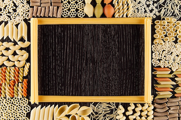 Assortment italian dry pasta on dark brown wooden board with blank copyspace as decorative frame background