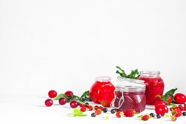 Assortment of jams, seasonal fresh berries and fruits on white background