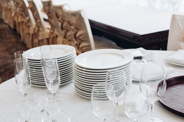 Assortment of kitchenware on white table.view over white round table with stacks of white plates, empty champagne flutes and glasses with bottles of water and ice buckets.