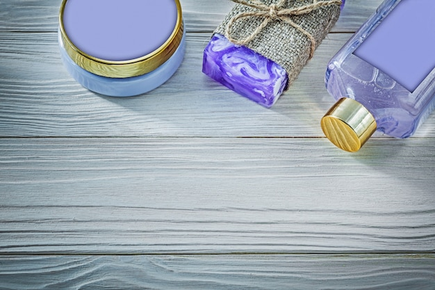 Assortment of lavender handmade soap shower gel and body lotion on wooden board spa concept