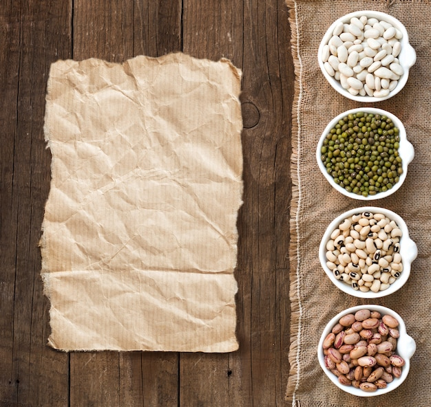 Assortment of legumes in bowls on wooden table top view with paper copy space
