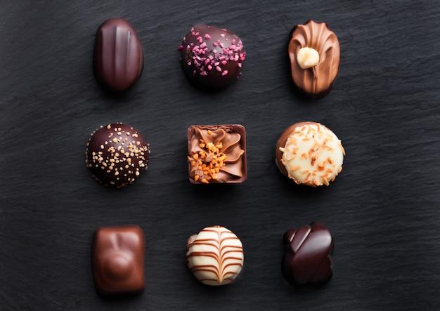 Assortment of luxury white and dark chocolate candies variety on black stone background