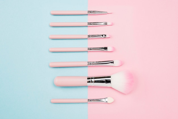 Assortment of make-up brushes on bicolor background