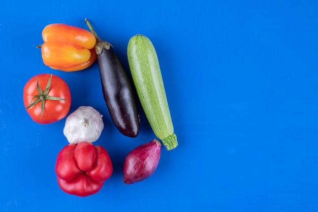 Assortimento di molte verdure mature fresche su superficie blu