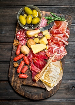 Assortment of meat snacks on board with olives and parmesan.