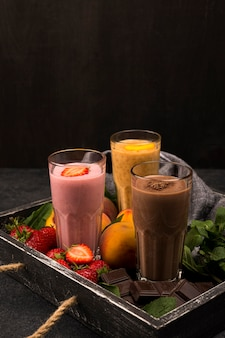 Assortment of milkshake glasses on tray with chocolate and fruits