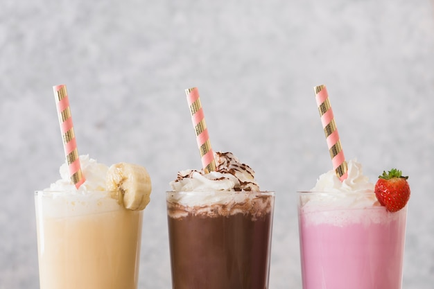 Assortment of milkshakes with straws