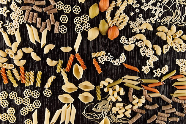 Assortment mix of traditional macaroni on dark brown wooden board as  decorative paste background
