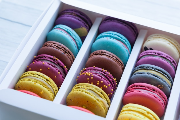 Assortment of multicolored macaroon different lie in the cardboard box with the top view.