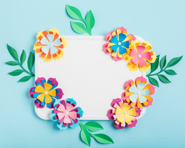 Assortment of multicolored paper spring flowers on whiteboard