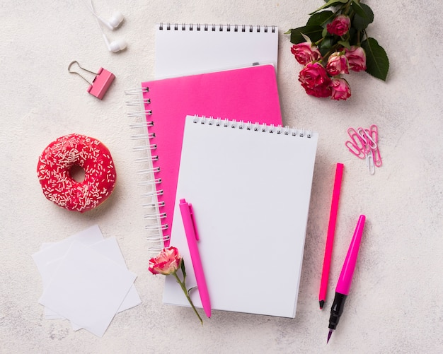 Assortment on notebooks with doughnut and bouquet of roses