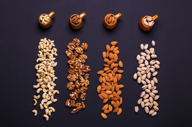 Assortment of nuts on a black slate - healthy snack.