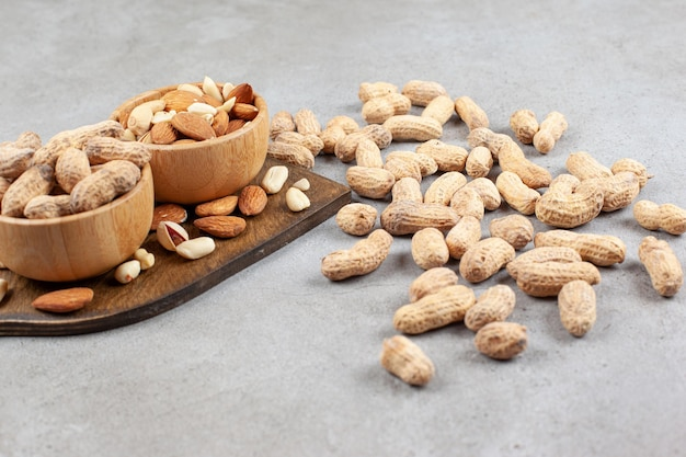 Assortment of nuts in bowls on wooden board and scattered on marble background. high quality photo