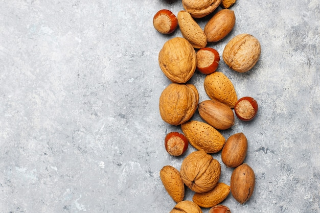 Assortment of nuts on concrete surface.hazelnuts, walnuts, pecans, peanut,almonds,top view