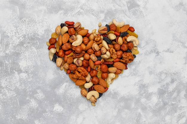 Assortment of nuts shape of heart cashew, hazelnuts, walnuts, pistachio, pecans, pine nuts, peanut, raisins.top view