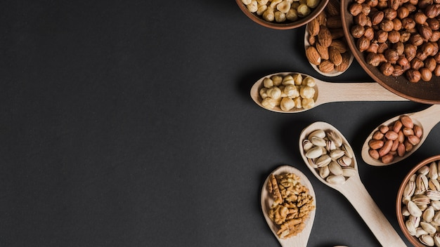 Assortment of nuts in spoons and bowls