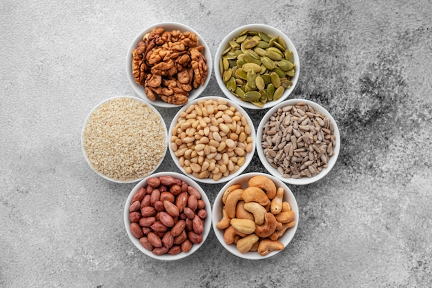Assortment of nuts in white saucers on a concrete background. food mix background, top view, copy space, banner