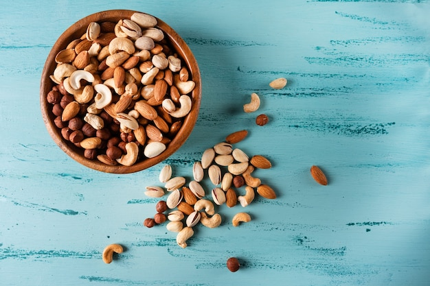 Assortment of nuts in wooden bowl on blue wooden table. cashew, hazelnuts, almonds.