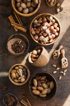 Assortment of nuts in a wooden bowl, on a wooden table. pecans, hazelnuts, almonds, pine nuts, brazil nut, cashews in shell. top view, flat lay.