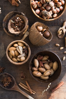 Assortment of nuts in a wooden bowl, on a wooden table. pecans, hazelnuts, almonds, pine nuts, brazil nut, cashews, top view, flat lay.