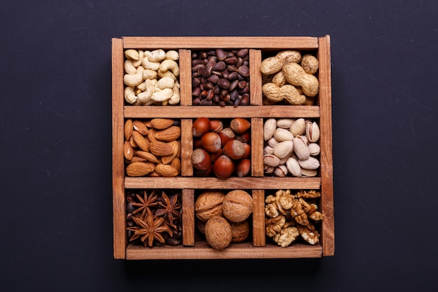 Assortment of nuts in a wooden box on a black slate - healthy snack.