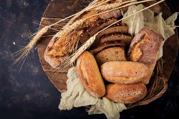 Ассортимент хлеба и булочки на деревянной поверхности. вид сверху. плоская планировка