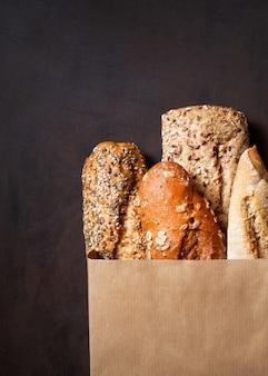 Ассортимент испеченного хлеба, хрустящий французский багет, буханки коричневого и белого зерна пшеницы, семена в упаковке.