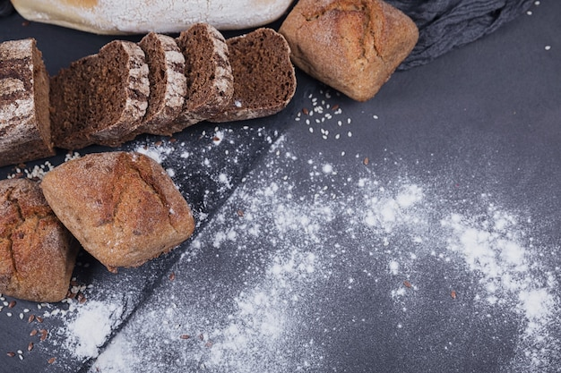어두운 배경에 구운 빵의 구색입니다. 베이커리 및 식료품 식품 매장 개념입니다. 텍스트를 위한 공간이 있는 플랫 레이