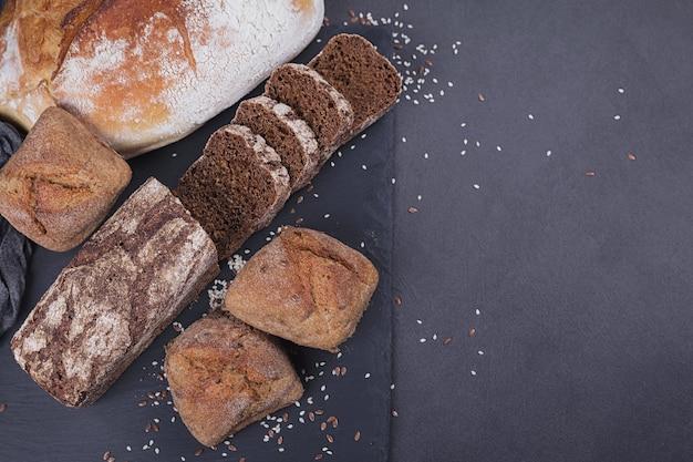 어두운 배경에 구운 빵의 구색입니다. 베이커리 및 식료품 식품 매장 개념입니다. 텍스트를 위한 공간이 있는 상위 뷰