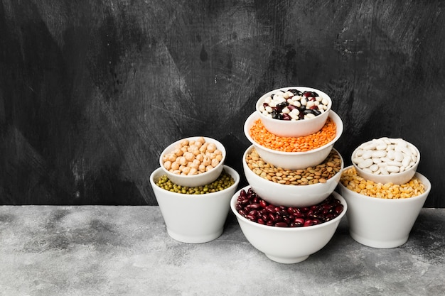 灰色のスペースに豆の品揃え(赤レンズ豆、緑レンズ豆、ひよこ豆、エンドウ豆、小豆、白豆、ミックス豆、緑豆)。コピースペース。フードスペース