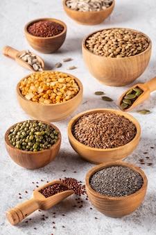 白いコンクリートの背景に豆、種子、マメ科植物の品揃え。