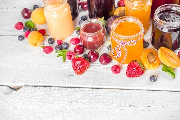 베리와 과일 잼의 구색. 다양한 계절 여름 베리와 과일 잼, 마멀레이드, 콩피츄어 세트. 흰색 나무 배경 복사 공간