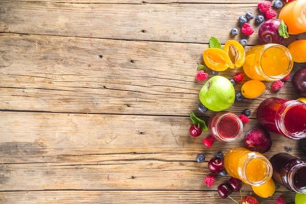 베리와 과일 잼의 구색. 다양한 계절 여름 베리와 과일 잼, 마멀레이드, 콩피츄어 세트. 나무 소박한 배경 복사 공간