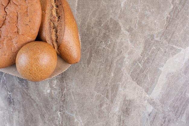 Ассортимент буханок хлеба на деревянной доске на мраморе.