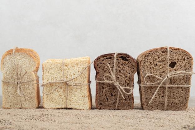 Ассортимент хлеба, перевязанный веревкой на мешковине. фото высокого качества