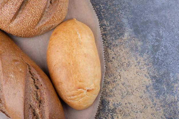 Ассортимент видов хлеба на деревянной доске на мраморной поверхности