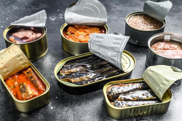Ассортимент банок, консервов из разных видов рыбы и морепродуктов. черный фон.
