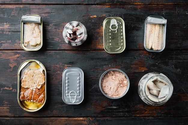 Ассортимент банок консервов с разными видами рыбы, на старом темном деревянном столе