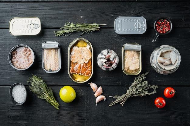 Ассортимент банок консервов с набором различных видов рыбы, на черном деревянном столе