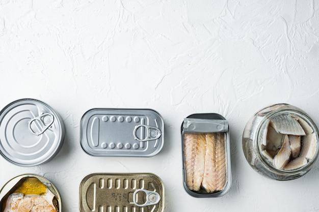 Ассортимент банок консервов с набором разных видов рыбы, на белом