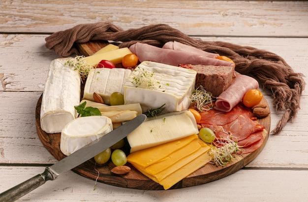 テーブルの上の木製トレイにチーズとハムの盛り合わせ