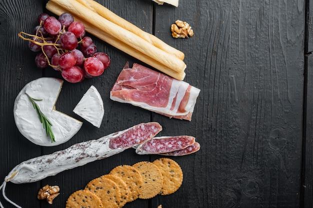 Ассортимент сырных и мясных закусок, на черном деревянном столе, вид сверху