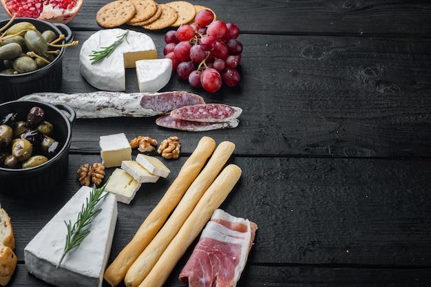 텍스트 복사 공간이 있는 검은색 나무 테이블에 다양한 치즈와 고기 전채 세트