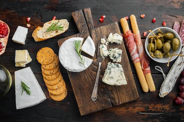 Ассортимент сырных и мясных закусок, на темном деревянном фоне, вид сверху