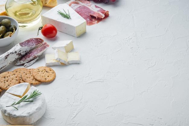 Ассортимент сырных и мясных закусок, на белом